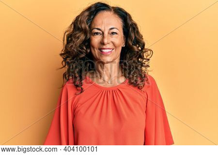 Middle age hispanic woman wearing casual clothes looking positive and happy standing and smiling with a confident smile showing teeth