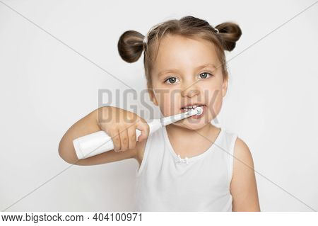 Little Cute Blond Girl Brushing Her Teeth With Electric Toothbrush. Oral Teeth Care And Caries Preve