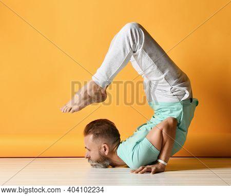 Mature Sporty Bearded Grey-haired Man Wearing Sportswear Practicing Yoga In Vrischikasana Scorpion A