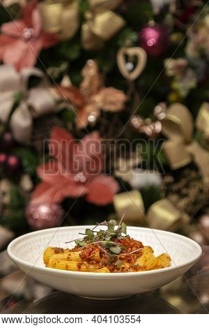 Rigatoni Pasta With Sugo Sauce And Lamb Ragout, With Coriander Leaves On Top. Christmas Background.