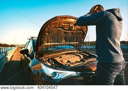 Stressed Man Having Trouble With His Broken Car On The Highway Roadside. Man Looking Under The Car H