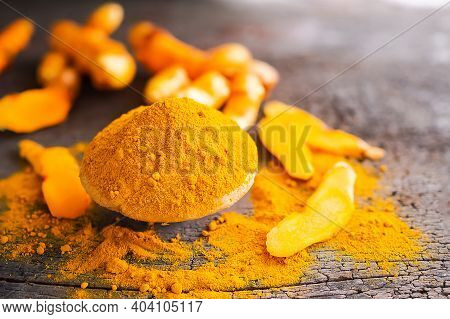 Turmeric Powder On Cup With Slice Raw Turmeric On Wood Background. Thai Herbs Concept.