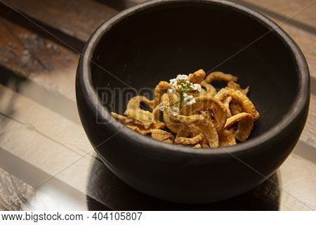 Bowl With Delicious Pork Cracklings On The Table