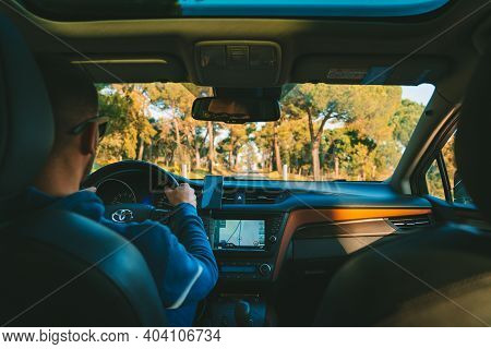 Young Man Driving Toyota Car At Sunset. Man Using Navigation System While Driving A Car. Lisbon, Por