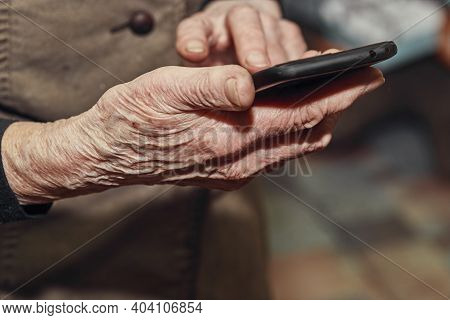 Old Womans Wrinkled Hands Hold A Modern Mobile Phone
