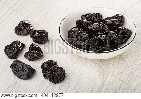 Dried Black Plums In White Bowl, Few Prunes On Wooden Table