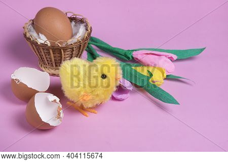 Toy Easter Chick Creacking From Eggshell On Pink Background.  Chick Hatching From Cracked Chick Egg.
