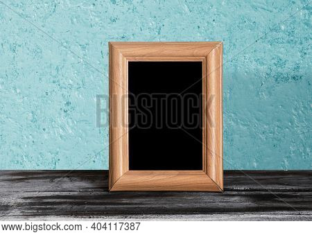 wooden photo frame on table, blue wall
