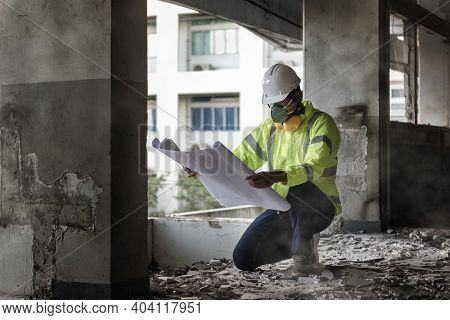 Civil Engineer People Wearing Face Mask And Safety Helmet While Looking To Detail In Drawing On Cons
