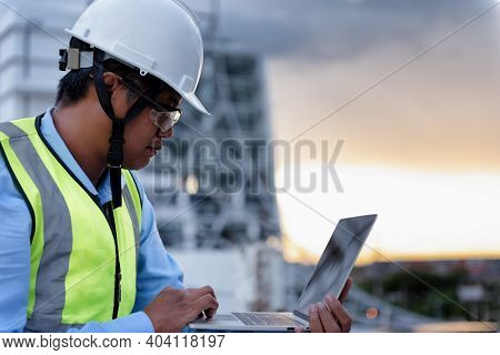 Civil Engineer Wearing High Visibility Safety Vest And Helmet While Using Laptop Looking To Drawing