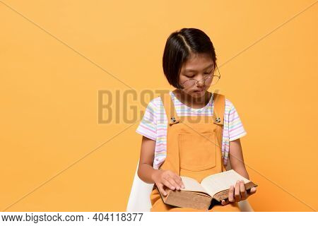 Asian Female Kid Who Wear Glasses Holding Dictionary Book And Concentrated Reading While Sitting Cha