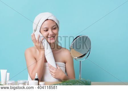 Beautiful Asian Young Woman Smiling And Touching Face With Towel While Looking At Mirror. Banner Bac