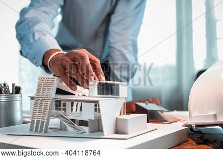 Hand Of Asian Architect-designer Holding The Part Of The Model Of Modern Box House While Thinking Ab