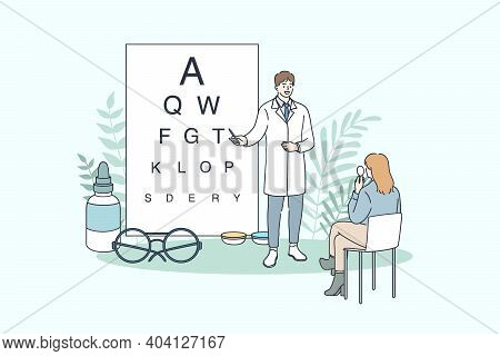 Ophthalmology And Ophthalmologist Concept. Young Man Doctor Ophthalmologist Making Eye Test Using Ch
