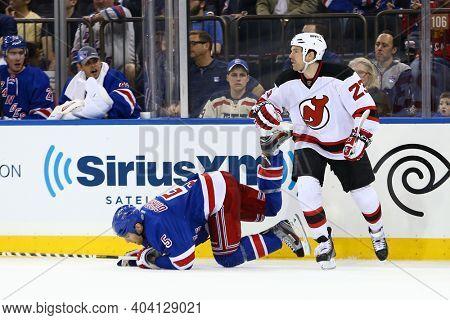 NEW YORK-APR 27: New York Rangers defenseman Dan Girardi (5) trips over New Jersey Devils center David Clarkson (23) at Madison Square Garden on April 27, 2013 in New York City.