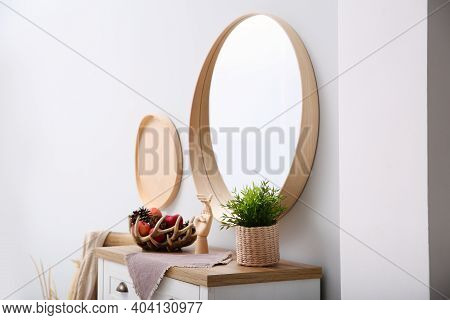 Round Mirror And Chest Of Drawers Near Grey Wall In Hallway. Interior Design
