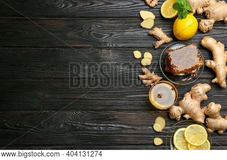 Ginger And Other Natural Cold Remedies On Black Wooden Table, Flat Lay. Space For Text