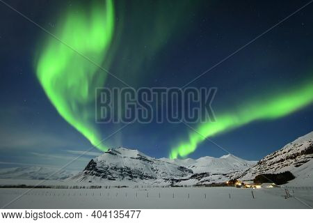 Intense Northern Lights Or Aurora Borealis Or Polar Lights And Morning Dawn On Night Sky Over Icy La