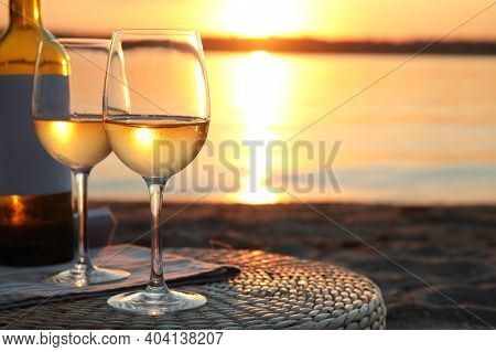 Bottle And Glasses Of Delicious Wine On Riverside At Sunset
