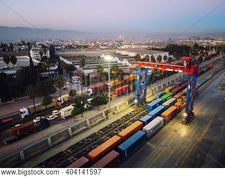 Stacked Cargo Containers And Overhead Gantry Crane. Aerial View. Mersin, Turkey - December 2020
