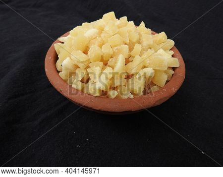 Yellow Color Jaggery Slices Or Cut Pieces In A Sand Plastic Bowl And Plastic Cup Isolated On Black B