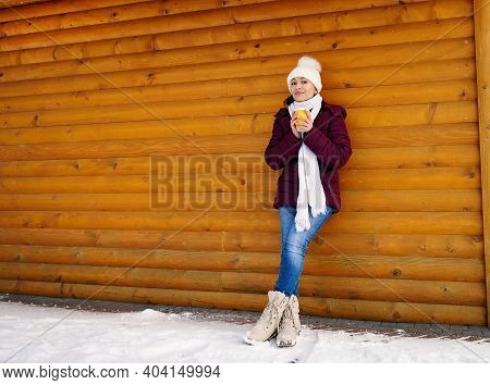 Portrait Of A Full-length Young Woman In Warm Clothes Leaning Against A Wooden Wall Of A Log Cabin A
