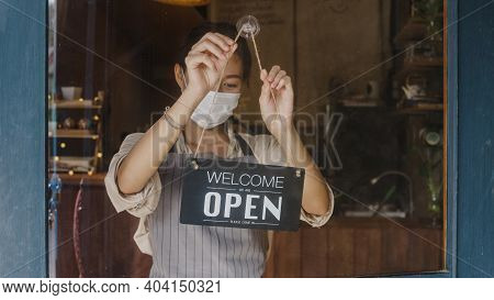 Young Asia Girl Wear Face Mask Turning A Sign From Closed To Open Sign On Door Looking Outside Waiti
