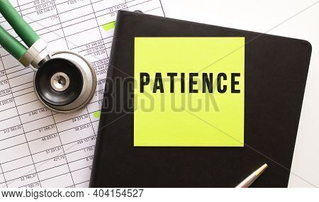 Black Notebook With Colored Sticker With The Inscription Patience. Nearby Is A Phonendoscope. Close-