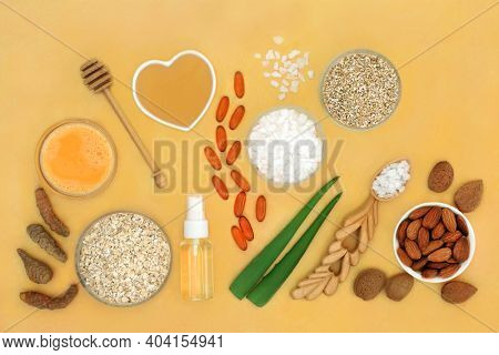 Alternative natural skincare beauty treatment ingredients used to treat skin ailments including eczema, psoriasis, acne, sunburn and skin infections. Flat lay on mottled yellow background.