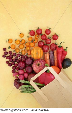 Fresh fruit and vegetable in a grocery bag high in lycopene for heart health also high in anthocyanins antioxidants, dietary fibre, vitamins and minerals. Healthy eating concept. On mottled yellow.