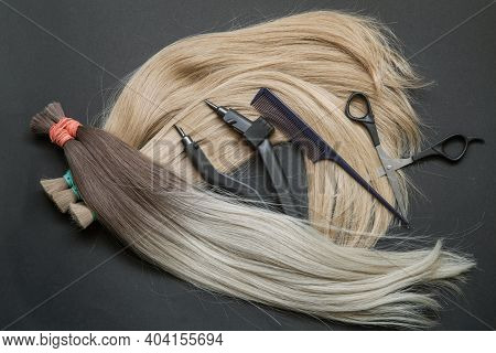 A Large Strand Of Hair With A Thin Comb-scissors Device For Encapsulating On A Black Background. . H