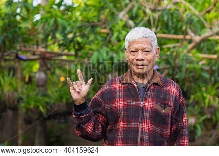 Portrait Of An Elderly Man Showing Fingers Symbol Love While Standing In A Garden. Space For Text. C