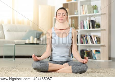 Front View Portrait Of A Disabled Woman With Neck Brace Doing Yoga Exercise At Home