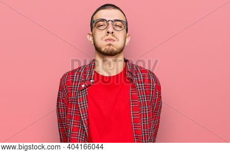 Hispanic young man wearing casual clothes puffing cheeks with funny face. mouth inflated with air, crazy expression.