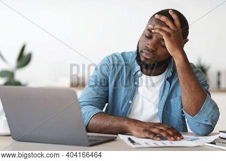 Stressed Black Male Entrepreneur Having Problems At Work. Depressed African American Man Sitting Ups