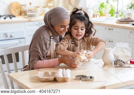 Adorable Little Girl And Her Muslim Mom Cooking In Kitchen, Kneading Dough For Cookies Together. Hap