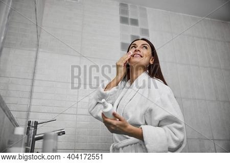 Happy Female Using Face Cleanser In Bathroom