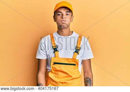 Young handsome african american man wearing handyman uniform over yellow background puffing cheeks with funny face. mouth inflated with air, crazy expression.