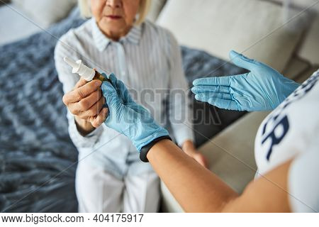 Caretaker Passing The Nasal Spray To Her Patient