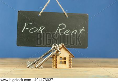 Real Estate Concept. House for rent. Real old blackboard write for rent with miniature house