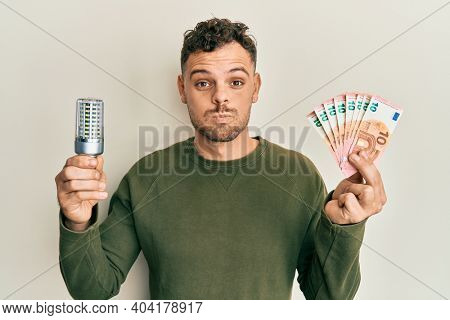 Young hispanic man holding led bulb and euros banknotes puffing cheeks with funny face. mouth inflated with air, catching air.