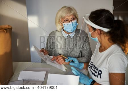 Caretaker Looking At A Female Pensioner With A Utility Bill