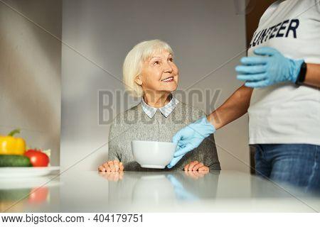 Pensioner Smiling At A Caretaker Serving Her Breakfast