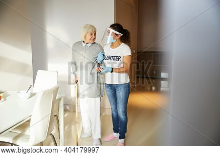 Smiling Pensioner Looking At Her Caregiver In A Face Shield