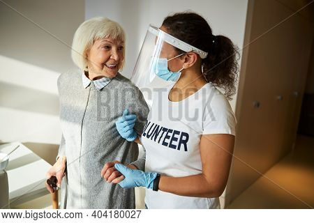 Cheerful Pensioner Standing Supported By Her Caretaker