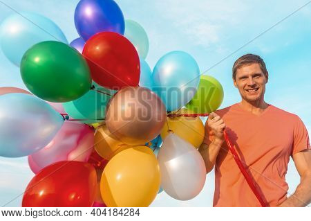 Happy Guy Running Along The Beach With Colored Balloons. Man Holding A Lot Of Colored Balloons.