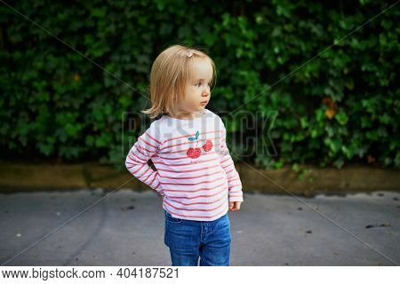 Confused Or Uncomfortable Toddler Girl Outdoors. Shy Kid On A Street