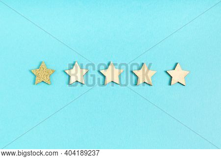 One Star Rating, One Gold Glittery Star And Four Wooden Stars On A Blue Background
