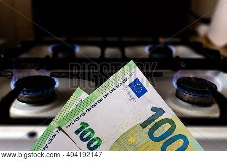 Money And Stove.burning Stove Flame And One Hundred Bills Two Denominations.close Up.