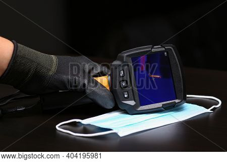 The Thermal Imager Inspection Camera And Protective Mask Lie On The Surface To Check The Temperature